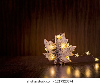 Natural maple leaf Christmas ornament wrapped in lights on a dark wood background.
