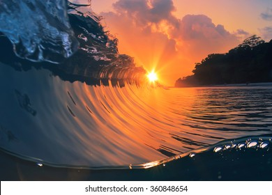 Natural marine design postcard. Beautiful colored breaking surfing ocean wave rolling down at sunset time.