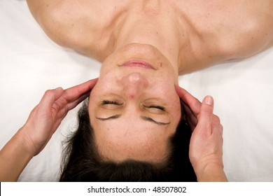 a natural mature woman having a massage at jaw and at her masseters