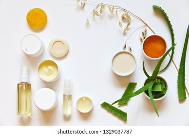 Natural medicinal bio cosmetics with aloe vera juice, honey and oats milk for face and body skin care: creams, gels, soap, scrub, lotion and spray on a white background. Flat lay, copy space