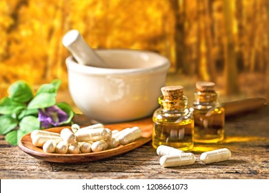Natural medicine capsule pill with herb, essential oil and ceramic mortar on wooden background for alternative medical concept.