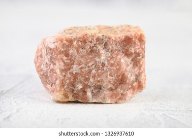 Natural mineral rock specimen - pink marble from Slyudyanka, Baikal, Russia on white cement background.