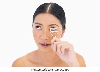 Natural model using eyelash curler looking up on white background
