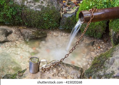 Natural mountain stream in the woods. Mug on iron chains.