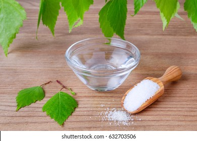 natural mouthwash bowl with xylitol water and wood scoop with birch sugar and leafs on wooden background