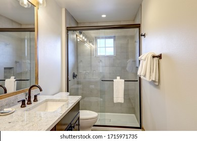 Natural new classic bathroom interior with new glass and ceramic tiles walk in shower and grey walls with white towels.