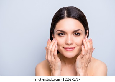 Natural nude charming woman applying lotion cream on cheekbones for flawless smooth soft skin, perfection anti-aging enhancement concept, isolated on grey background, copy space, empty place