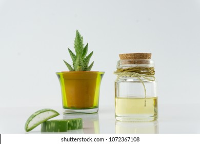 Natural oil in bottle and fresh aloe vera  cut into pieces on white floor.