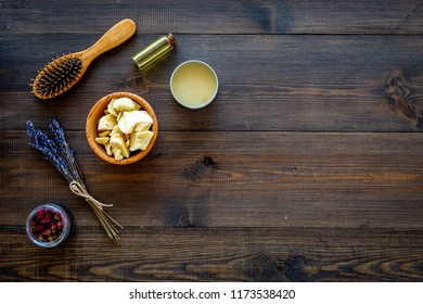 Natural oil for hair. Jojoba, argan, coconut oil near bunch of lavender and hairbrush on dark wooden background top view copy space
