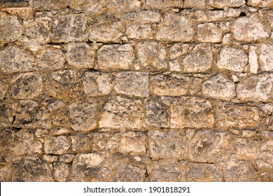 Natural old beige stone wall textured background. Close up. Copy space.