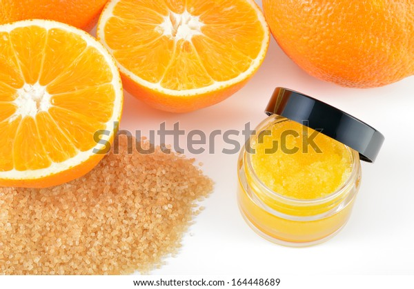 Natural orange sugar lip scrub on white background with reflection. Orange cosmetic in a glass jar with oranges in a background.