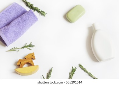 Natural organic bath products. Purple towel, green soap, shampoo bottle and rosemary leaves. Flat lay beauty background. Copy space. Mockup for design