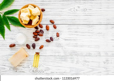 Natural organic cosmetics based on cocoa butter. Cocoa beans and cocoa butter, soap, cream, oil or lotion in small bottles on grey background top view copy space