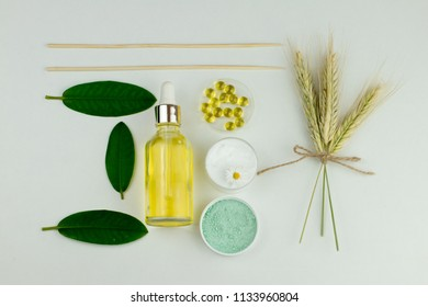 Natural organic cosmetics based on oil or lotion in bottles, sea salt, wheat spikelets, chamomile cream, liquid capsules. Top view image