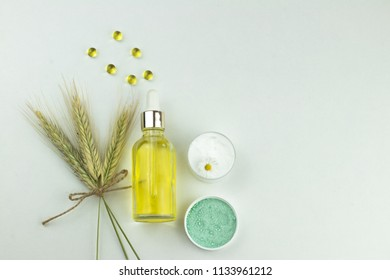 Natural organic cosmetics based on oil or lotion in bottles, sea salt, chamomile cream, liquid capsules. Top view image, copy space
