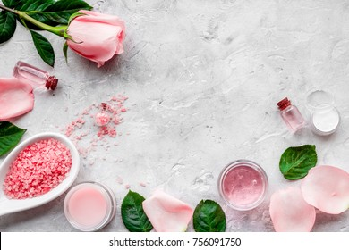 Natural organic cosmetics with rose oil. Cream, lotion, spa salt on grey background top view copyspace