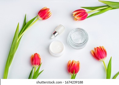 Natural organic homemade cosmetics concept. Skin care, remedy and beauty products: containers with cream and serum among spring red tulip flowers on white background. Flat lay, copy space for text