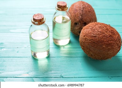 Natural organic product. Bottles with coconut oil on  bright  turquoise  wooden background. Selective focus. Place for text.