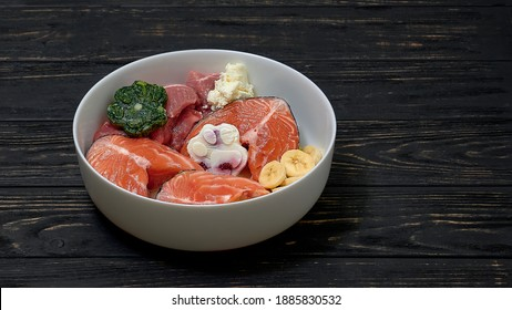 Natural organic raw dog food in bowl. Salmon, pork, egg, fruits and vegetables, food supplement.