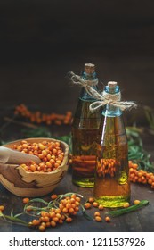 Natural, organic sea-buckthorn berry in bowl and sea buckthorn oil in glass vintage bottle on dark wooden background. Dark rustic style, natural remedy.