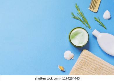 Natural organic spa cosmetics on a blue background. Moisturizing and nourishing body cream, shampoo, beige towel, shells and rosemary herbs on a blue background