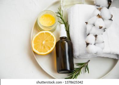 Natural organic spa ingredients with lemon, rosemary branches, balm jar, face mist spray bottle, cotton towel with cotton buds