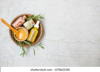 Natural organic spa ingredients with manuka honey,clay powder, lemon oil bottle, rosemary branches, bath sea salt in wooden plate top view,  home spa
