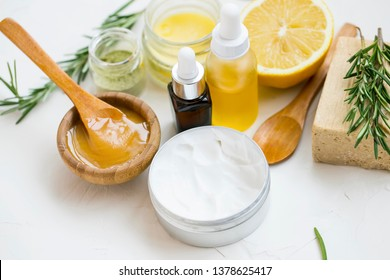 Natural organic spa ingredients with manuka honey, essential oil bottle, clay powder ,body lotion, bath salt, rosemary branches, natural soap, lemon