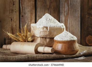 Natural, organic, wholegrain wheat meal in a paper bag, a rolling pin, wheat ears on an old wooden background