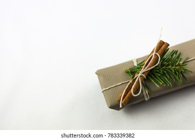 Natural package of gift for Christmas or birthday, dry cinnamon and green little branch, brown simple paper and a cord