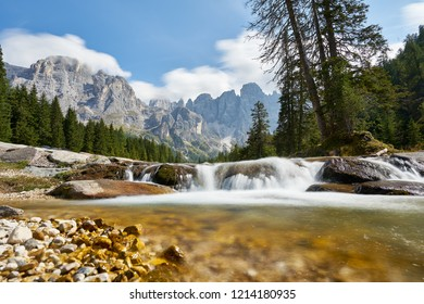 natural park Paneveggio in the dolomites of Trentino Italy. With forest mountains creek and view Pale di San Martino