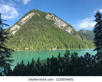 Natural park. Rowing boat on the lake near mountains and trees