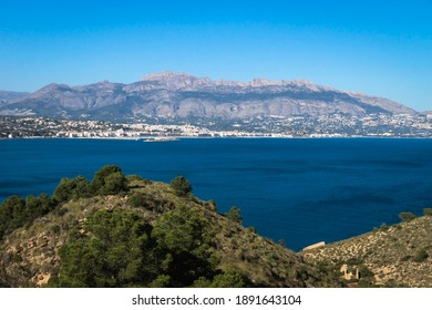 Natural park 'Serry Gelada' with view to Altea under mountainrange and ruin of ocher mine along the coast of Albir, Costa Blanca, Spain