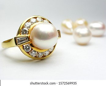 natural pearl ring with diamond on white background.