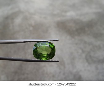 Natural peridot gemstone with cement wall,gem background