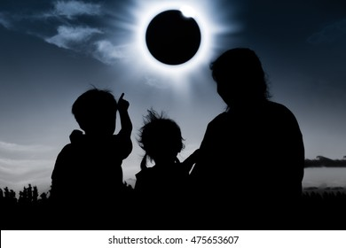 Natural phenomenon. Silhouette back view of mother and child sitting and relaxing together. Boy pointing to solar eclipse on dark sky background. Happy family spending time together. Outdoor.