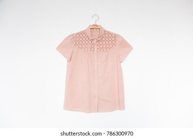 Natural pink colour blouse is clothes hanger on white background.