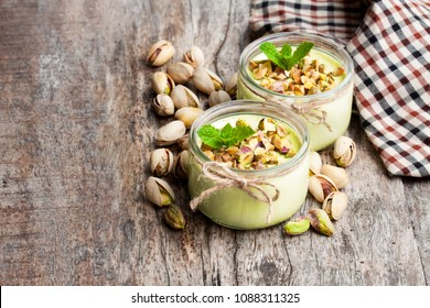 Natural  pistachio yogurt in a small glass jar on wooden table