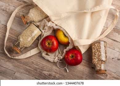 Natural, plastic free recycled textile produce bag for carrying fruit or vegetables on a wooden surface. Reusable cotton textile bags and glass small containers for zero waste shopping or storage.