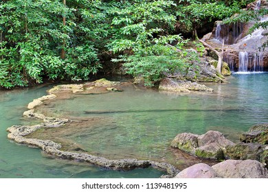 Natural ponds with clear water and fish swimming around in the rain forest of Erawan Waterfall National Park, Kanjanaburi, Thailand