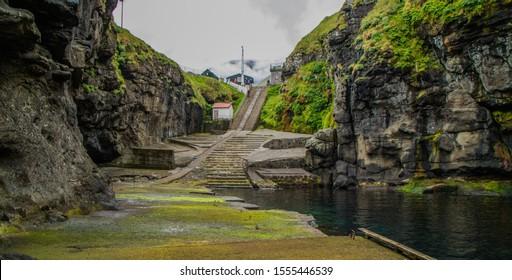 Natural port in Gjògv ( Gjogv Port) on Eysturoy Island, Faroe Islands / Naturalny port w Gjògv ( Gjogv Port) na wyspie Eysturoy, Wyspy Owcze - Shutterstock ID 1555446539