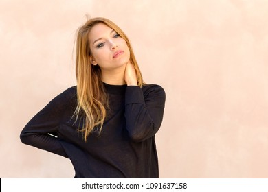Natural portrait of a beautiful young woman with her hand on her neck and head tilted to the side gazing thoughtfully at the camera over a neutral studio background