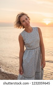 Natural portrait of a blonde woman in a dress near the sea