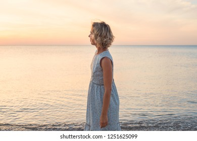 Natural portrait of a blonde woman in a dress near the sea in profile