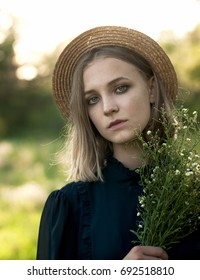 Natural portrait of a girl in a straw hat with a bouquet of wild flowers