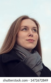 Natural portrait of a young woman with long hair looking into the distance