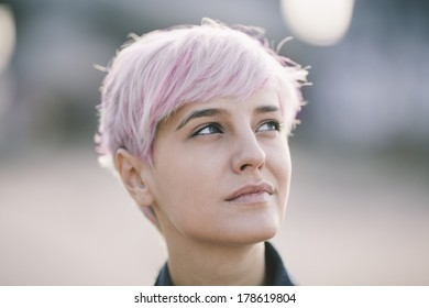 natural portrait of young woman with pink hair
