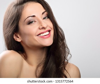 Natural positive nude day makeup toothy smiling woman with long hair style. Skincare concept. Closeup portrait on blue background with empty copy space.