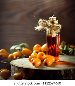 Natural product: Sea-buckthorn oil in a small decorative bottle surrounded by ripe orange berries olbepiha on a wooden stand.