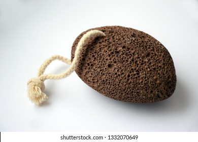 Natural pumice stone with white rope on light white background. Pedicure and spa concept.
